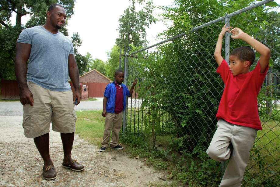 Houston Texans defensive lineman Earl Mitchell, left, talks to De'aurion Caldwell, center, and Christopher McAdams, while visiting the neighborhood where he grew up Tuesday, Sept. 11, 2012, in Houston. Photo: Brett Coomer, Houston Chronicle / © 2012 Houston Chronicle