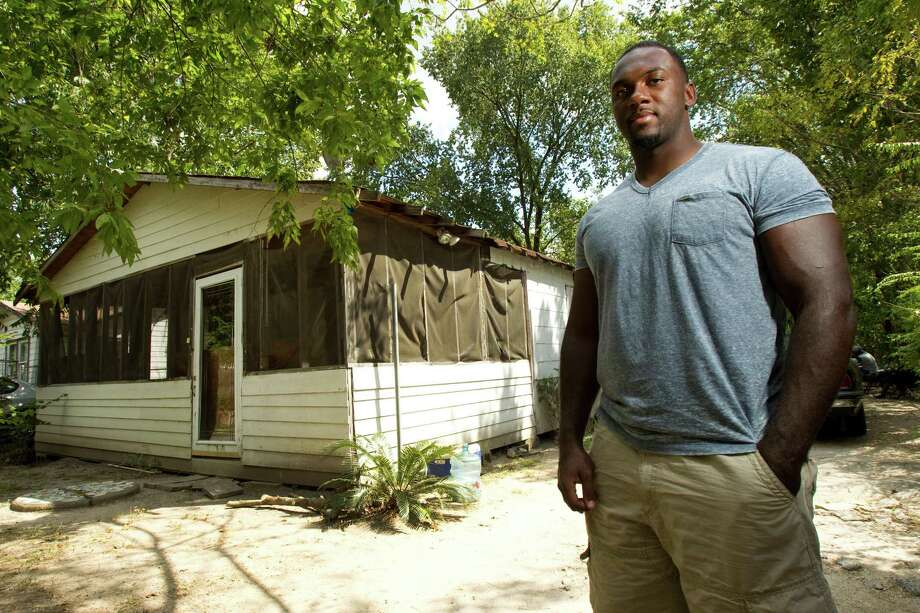 Houston Texans defensive lineman Earl Mitchell poses for a portrait outside the former home of his grandmother, Narnie Mitchell, where he lived through much of his childhood, during a visit to the house Tuesday, Sept. 11, 2012, in Houston. Mitchell's grandmother died in 2001. Photo: Brett Coomer, Houston Chronicle / © 2012 Houston Chronicle
