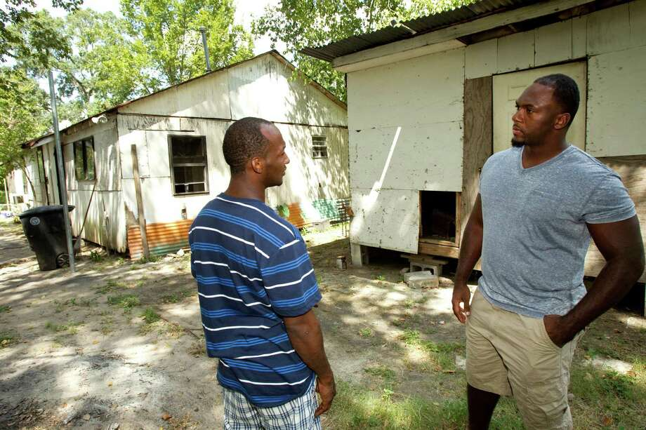 Houston Texans defensive lineman Earl Mitchell, right, talks to his cousin, DeWayne Mitchell, outside the former home of his grandmother,  Narnie Mitchell, where he lived through much of his childhood, during a visit to the house Tuesday, Sept. 11, 2012, in Houston. Photo: Brett Coomer, Houston Chronicle / © 2012 Houston Chronicle