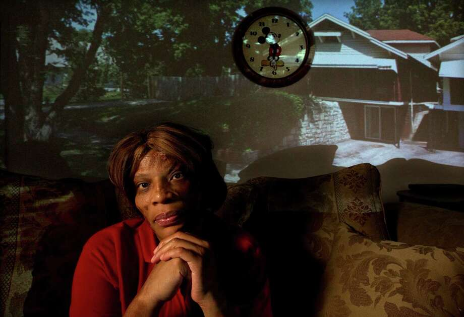 A projection in her Houston home shows the Kansas house where Amy Woodard-Davis was born, then left in a trash fire. Photo: Johnny Hanson / © 2012  Houston Chronicle