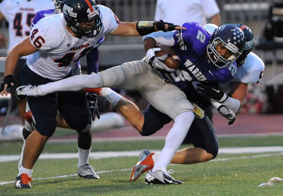 Warren punt returner Eric Castilleja (2) is tackled by Joshua Lewis of Brandeis during high-school football action at Gustafson Stadium on Saturday, Sept. 15, 2012. Photo: Billy Calzada, San Antonio Express-News / © San Antonio Express-News