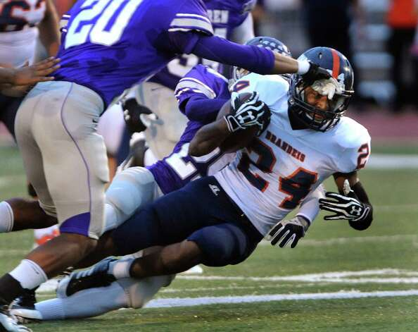 Brandeis runner William Hughes (24) is tackled after a short gain against Warren during high-school football action at Gustafson Stadium on Saturday, Sept. 15, 2012. Photo: Billy Calzada, San Antonio Express-News / © San Antonio Express-News