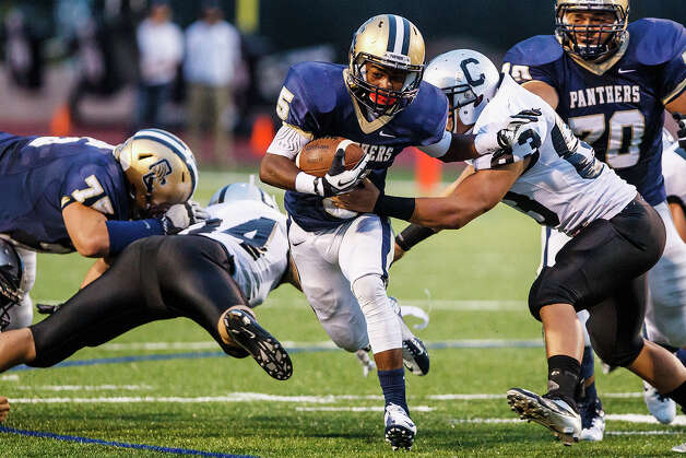 O'Connor running back Tre Johnson (center) tries slip past Clark's Timothy Rodriguez as he makes his way through the line of scrimmage during the first quarter of their game at Farris Stadium on Sept. 14, 2012.  Johnson ran for 325 yards and four touchdowns as O'Connor beat the Cougars 52-19 in their District 27-5A opener.  MARVIN PFEIFFER/ mpfeiffer@express-news.net Photo: MARVIN PFEIFFER, Express-News / Express-News 2012
