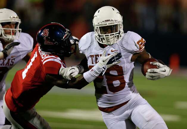 OXFORD, MS - SEPTEMBER 15:  Malcolm Brown #28 of the Texas Longhorns fights off the tackle of Dehendret Collins #1 of the Ole Miss Rebels at Vaught-Hemingway Stadium on September 15, 2012 in Oxford, Mississippi. Photo: Scott Halleran, Getty Images / 2012 Getty Images