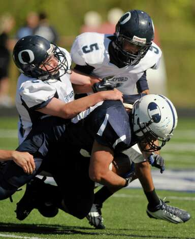 Immaculate's Steven Ghossaini runs for a first down while under pressure from Oxford's Noah Lisewski, left, and Owen Diaz during their game at Immaculate High School in Danbury on Saturday, Sept. 15, 2012. Oxford won, 35-0. Photo: Jason Rearick / The News-Times