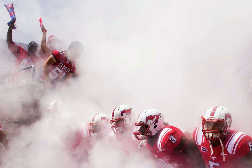 Southern Methodist players prepare to take the field through a cloud of smoke before an NCAA footbal