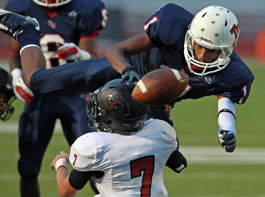 Rough Rider receiver Marcel Mayes looses grasp on the ball after a hit by Philip Shelton as Roosevelt hosts Canyon at Heroes Stadium on September 15, 2012. Photo: Tom Reel, Express-News / ©2012 San Antono Express-News