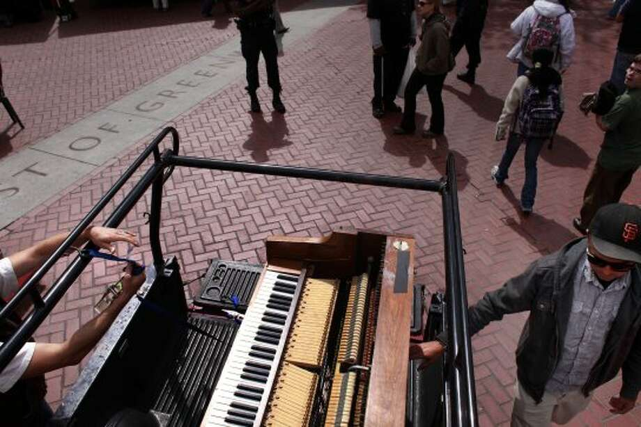 Kirby Lee Hammel and Jacob Alexander unload their upright piano and drum set at the Heart of the City Famers'  Market before performing as the musical duo know Clangin' and Bangin' in San Francisco, Calif. (Mike Kepka / The Chronicle)