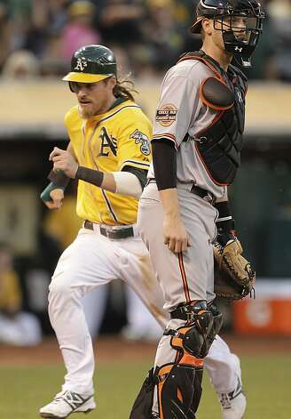 Oakland Athletics' Josh Reddick, left, scores behind Baltimore Orioles catcher Matt Wieters in the third inning of a baseball game Saturday, Sept. 15, 2012, in Oakland, Calif. Reddick scored on a double by Chris Carter. (AP Photo/Ben Margot) Photo: Ben Margot, Associated Press