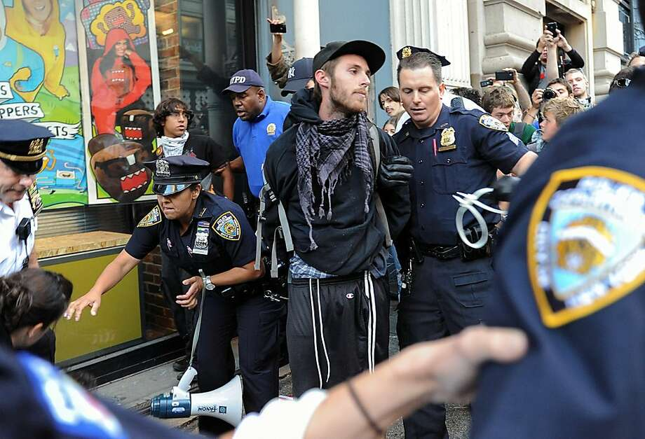 A person associated with the Occupy movement is arrested on a march down Broadway Street in New York enroute to Zuccotti Park, Saturday, Sept. 15, 2012. Monday marks the one year anniversary of the Occupy movement. (AP Photo/Stephanie Keith) Photo: Stephanie Keith, Associated Press