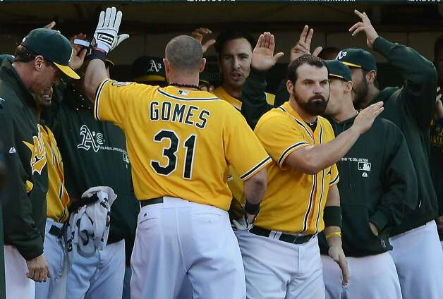OAKLAND, CA - SEPTEMBER 15:  Jonny Gomes #31 of the Oakland Athletics is congratulated by teammates after Gomes scored on an RBI single from Yoenis Cespedes #52 (not pictured) in the third inning against the Baltimore Orioles at O.co Coliseum on September 15, 2012 in Oakland, California.  (Photo by Thearon W. Henderson/Getty Images) Photo: Thearon W. Henderson, Getty Images