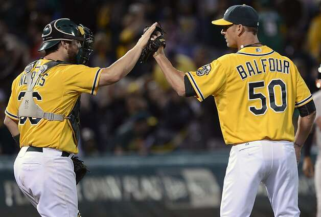 OAKLAND, CA - SEPTEMBER 15:  Grant Balfour #50 and Derek Norris #36 of the Oakland Athletics celebrate defeating the Baltimore Orioles 5 to 2 at O.co Coliseum on September 15, 2012 in Oakland, California.  (Photo by Thearon W. Henderson/Getty Images) Photo: Thearon W. Henderson, Getty Images