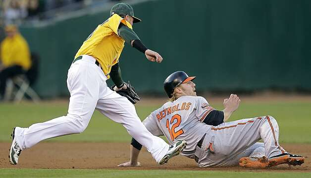 Baltimore Orioles' Mark Reynolds (12) is tagged out by Oakland Athletics third baseman Josh Donaldson in a rundown between second and third base in the second inning of a baseball game on Saturday, Sept. 15, 2012, in Oakland, Calif. (AP Photo/Ben Margot) Photo: Ben Margot, Associated Press