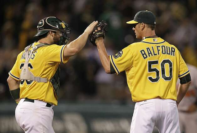 Oakland Athletics' Grant Balfour, right, celebrates with Derek Norris at the end of a baseball game against the Baltimore Orioles, Saturday, Sept. 15, 2012, in Oakland, Calif. (AP Photo/Ben Margot) Photo: Ben Margot, Associated Press