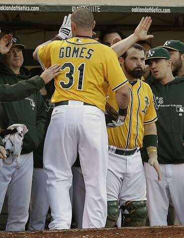 Oakland Athletics' Jonny Gomes (31) is congratulated after scoring against the Baltimore Orioles in the third inning of a baseball game on Saturday, Sept. 15, 2012, in Oakland, Calif. Gomes scored on a single by Yoenis Cespedes. (AP Photo/Ben Margot) Photo: Ben Margot, Associated Press