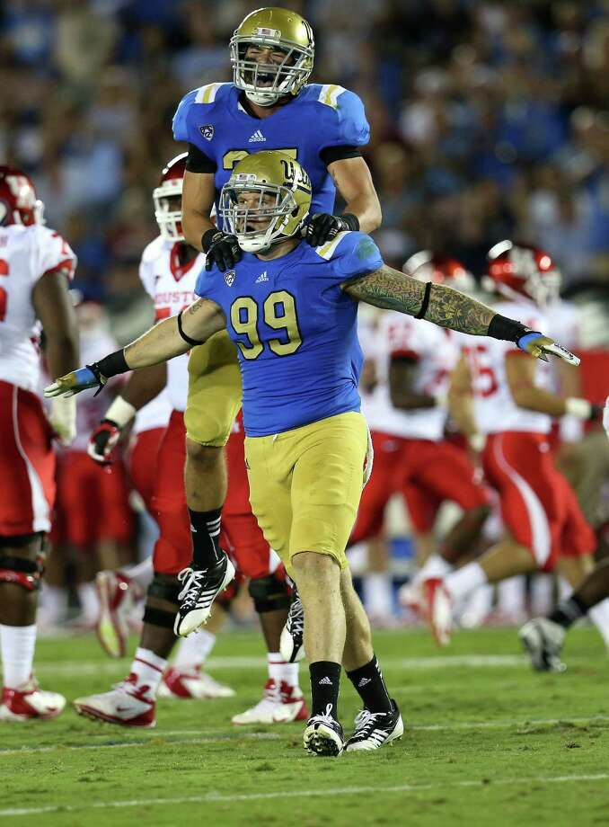 PASADENA, CA - SEPTEMBER 15: Defensive end  Cassius Marsh #99 and linebacker Jordan Zumwalt #35 of the UCLA Bruins celebrate after a Marsh sack against the Houston Cougars at the Rose Bowl on September 15, 2012 in Pasadena, California. Photo: Stephen Dunn, Getty Images / 2012 Getty Images