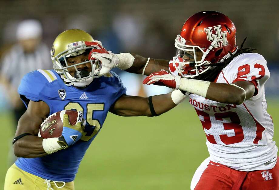 PASADENA, CA - SEPTEMBER 15: Running back Damien Thigpin #25 of the UCLA Bruins carries the ball against defensive back Trevon Stewart #23 of the Houston Cougars at the Rose Bowl on September 15, 2012 in Pasadena, California. An apparent facemask penalty was not called. Photo: Stephen Dunn, Getty Images / 2012 Getty Images