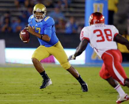 UCLA quarterback Brett Hundley, left, runs the ball as Houston defensive back Steven Aikens defends during the first half of an NCAA college football game, Saturday, Sept. 15, 2012, in Pasadena, Calif. (AP Photo/Mark J. Terrill) Photo: Mark J. Terrill, Associated Press / AP