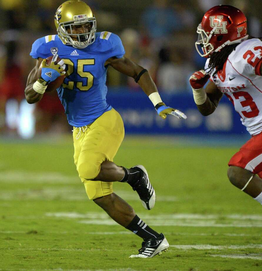 UCLA 37, UH 6UCLA wide receiver Damien Thigpen, left, avoids a tackle by Houston defensive back Trevon Stewart during the first half of their NCAA college football game, Saturday, Sept. 15, 2012, in Pasadena, Calif.  (AP Photo/Mark J. Terrill) Photo: Mark J. Terrill, Associated Press / AP