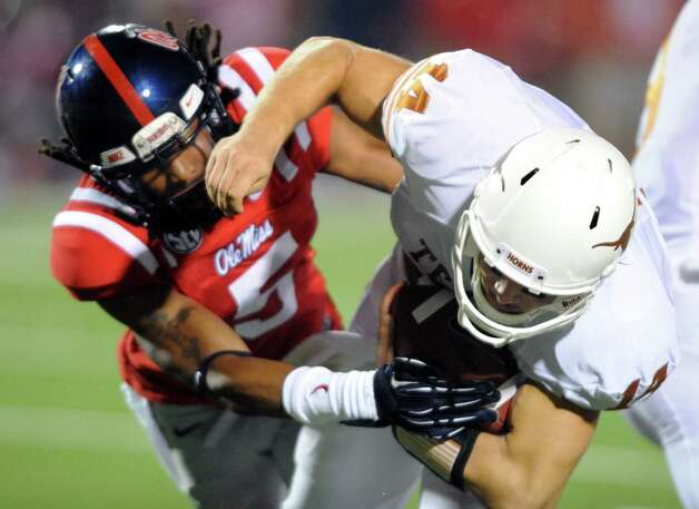 Texas'  David Ash (14) is tackled by Mississippi defensive back Frank Crawford (5) during their NCAA college football game at Vaught-Hemingway Stadium in Oxford, Miss. on Saturday, Sept. 15, 2012. (AP Photo/Oxford Eagle, Bruce Newman) Photo: Bruce Newman, Associated Press / Oxford Eagle