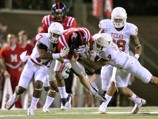 Mississippi quarterback Bo Wallace (14) is tackled by Texas' Adrian Phillips (17) and Kenny Vaccaro (4) during an NCAA college football game in Oxford, Miss., on Saturday, Sept. 15, 2012. (AP Photo/Oxford Eagle, Bruce Newman) MAGS OUT  NO SALES  MANDATORY CREDIT Photo: Bruce Newman, Associated Press / Oxford Eagle