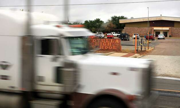 An oil industry truck travels along Tilden St. passing the Cotulla High School.  The oil industry in South Texas, and in Cotulla, is making the school district look wealthy and district officials will have to share that wealth with poorer districts.  Friday, Sept. 14, 2012. Photo: Bob Owen, San Antonio Express-News / © 2012 San Antonio Express-News
