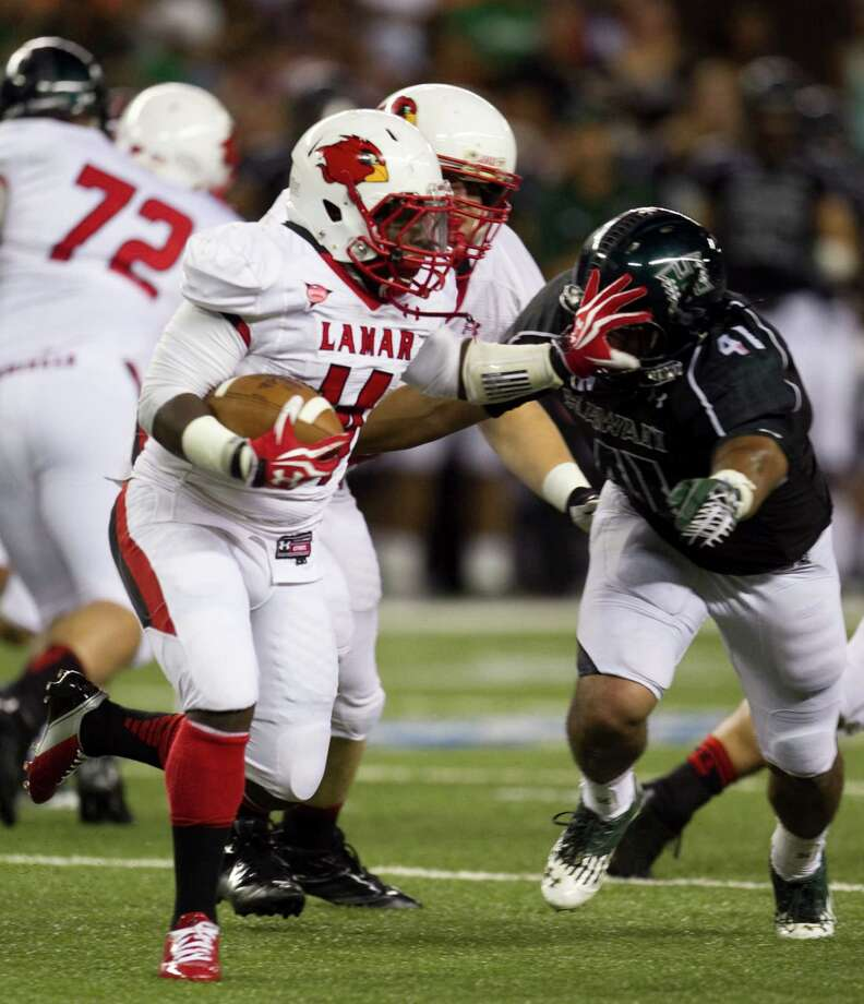Lamar running back DePauldrick Garett shoves off Hawaii linebacker Art Laurel during the second quarter of the NCAA game between the Lamar and Hawaii, Sept. 15, 2012 in Honolulu.  (AP Photo/Marco Garcia) Photo: Marco Garcia, FRE / FR132415 AP