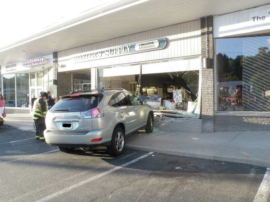 This Lexus SUV surged out of control Saturday and crashed into the front of the Painters Supply Store in the Compo Shopping Center. Photo: Westport Fire Department / Westport News contributed
