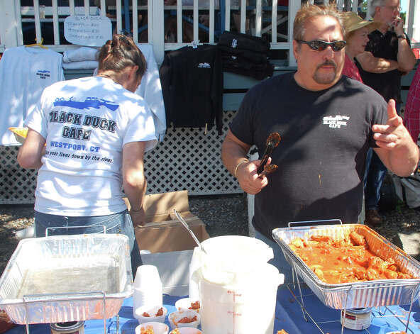 Glenn Ferrari, manager of the Black Duck Cafe, serves up spicy chicken wings to crowds at the Slice of Saugatuck festival on Saturday. Photo: Jarret Liotta / Westport News contributed
