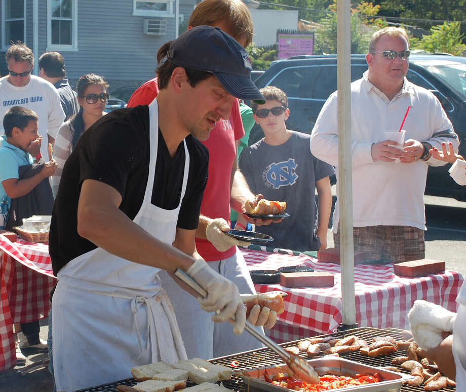 "Anthony Kusselmark, general manager of Rizzuto's restaurant, serves up sausage and peppers at the Slice of Saugatuck. ""It's great for downtown Saugatuck,"" he said of the festival in 2012. Photo: Jarret Liotta / Westport News contributed"