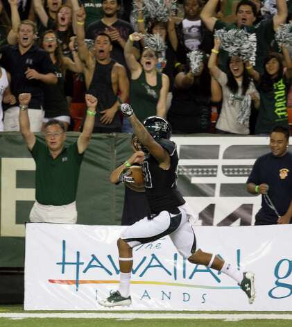After Hawaii special teams blocked a punt, Hawaii defensive back Ne'Quan Phillips returns the ball for a touchdown during the second quarter of the NCAA game between the Lamar and Hawaii, Sept. 15, 2012 in Honolulu.  (AP Photo/Marco Garcia) Photo: Marco Garcia, FRE / FR132415 AP
