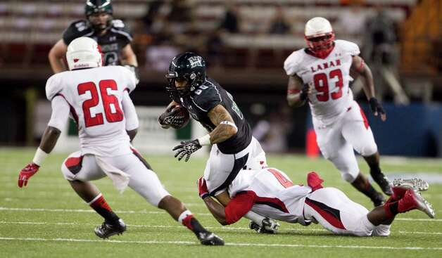 Hawaii wide receiver Jeremiah Ostrowski, center, gets pulled down by Lamar defensive back Tyrus McGlothen during the second quarter of the NCAA game between the Lamar and Hawaii, Sept. 15, 2012 in Honolulu.  (AP Photo/Marco Garcia) Photo: Marco Garcia, FRE / FR132415 AP