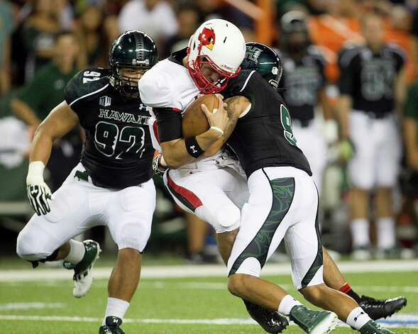 Lamar quarterback Ryan Mossakowski, center, gets sacked by Hawaii defensive back Bubba Poueu-Luna, right,  and defensive lineman Beau Yap, left, during the second quarter of the NCAA game between the Lamar and Hawaii, Sept. 15, 2012 in Honolulu.  (AP Photo/Marco Garcia) Photo: Marco Garcia, FRE / FR132415 AP