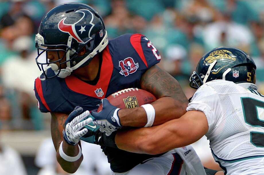 Houston Texans running back Arian Foster, left, is tackled after a short gain by Jacksonville Jaguars outside linebacker Russell Allen during the first half of an NFL football game, Sunday, Sept. 16, 2012, in Jacksonville, Fla. (AP Photo/Phelan M. Ebenhack) Photo: Phelan M. Ebenhack, Associated Press / FR121174 AP