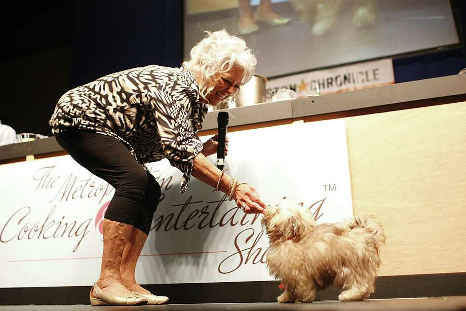 Paula Deen gives her new dog Lulu, a chocolate Javanese, a treat after doing a trick during the Metropolitan & Entertaining Show. Photo: Houston Chronicle