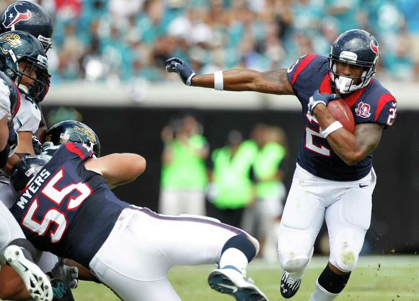 Houston Texans running back Arian Foster (23) finds a running lane behind the blocking of center Chr