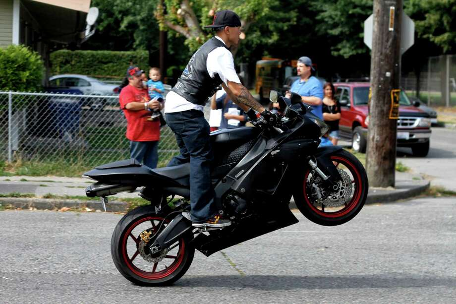 "A member of the Latino Riders ""pops a wheelie"" on his motorcycle. Photo: Sofia Jaramillo / SEATTLEPI.COM"