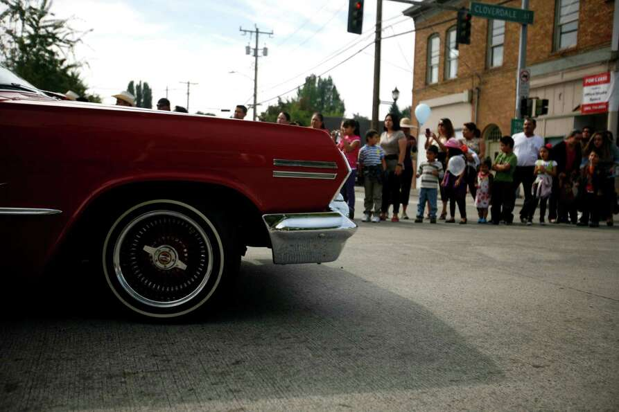 People are shown in the background as a lowrider car drives by during the Fiestas Patrias Celebratio