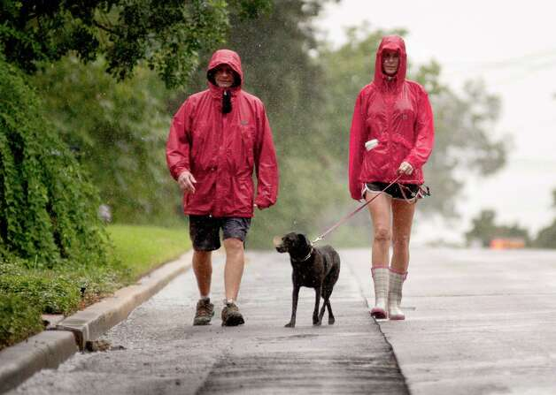 Alamo Heights resident Camille Earthman, right, walks her dog, Paco, in the rain with her neighbor, Paul Neidinger, Sunday, Sept. 16, 2012. Photo: Darren Abate, Darren Abate/For The Express-New
