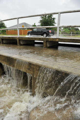 Rainwater drains off of Rowe Rd. on the northeast side during Sunday morning rain. Photo: For The Express-News