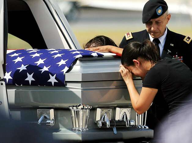 Liliana Montenegro cries over the casket of her brother, U.S. Army Warrant Officer Jose Luis Montenegro Jr., after his body arrived Sunday, Sept. 16, 2012 at McCreery Aviation in McAllen, Texas. Montenegro was stationed at Fort Bragg, N.C. and was serving his third tour of duty overseas when his helicopter was shot down in Afghanistan's Logar province. Nearly 2,000 American troops have been killed in the conflict since the 2001 invasion. (AP Photo/The Monitor, Gabe Hernandez) Photo: Gabe Hernandez, Associated Press / The Monitor