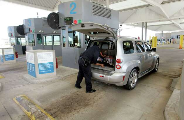 Customs officers inspect a vehicle at the port of entry in Donna, Texas Tuesday Sept.4,2012. The Donna bridge had 2 lanes of inbound traffic lanes open. With up to 40,000 trucks and 100,000 cars going through the toll booths each month, the Pharr International Bridge generates about $900,000 monthly, and is the envy of other area bridge operators including Donna who would love a chunk of the cross border commercial traffic. Photo: Delcia Lopez, SPECIAL TO THE EXPRESS NEWS / DELCIA LOPEZ PHOTOGRAPHY©