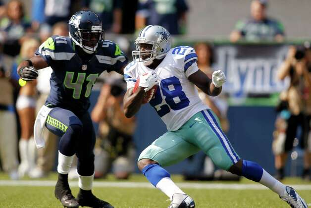 Dallas Cowboys' Felix Jones (28) rushes as Seattle Seahawks' Byron Maxwell defends in the first half of an NFL football game on Sunday, Sept. 16, 2012, in Seattle. (AP Photo/John Froschauer) Photo: John Froschauer, Associated Press / FR74207 AP