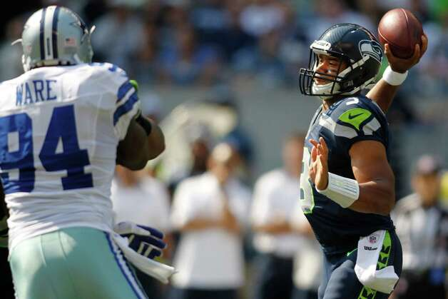 Seattle Seahawks quarterback Russell Wilson, right, throws under pressure from Dallas Cowboys' Demarcus Ware in the first half of an NFL football game, Sunday, Sept. 16, 2012, in Seattle. (AP Photo/John Froschauer) Photo: John Froschauer, Associated Press / FR74207 AP