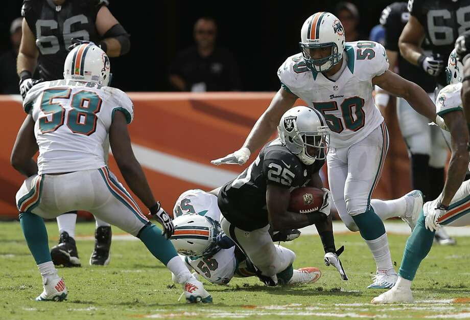 Oakland Raiders running back Mike Goodson (25) is tackled by Miami Dolphins outside linebacker Kevin Burnett (56) during the second half of an NFL  football game, Sunday, Sept. 16, 2012 in Miami. The Dolphins defeated the Raiders 35-13. Also shown are Miami Dolphins middle linebacker Karlos Dansby (58) and Miami Dolphins defensive end Olivier Vernon (50). (AP Photo/Lynne Sladky) Photo: Lynne Sladky, Associated Press