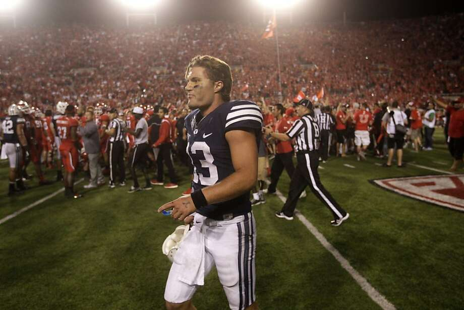 BYU quarterback Riley Nelson walks away from Utah fans who prematurely stormed the field twice in the Utes' win. Photo: Rick Bowmer, Associated Press