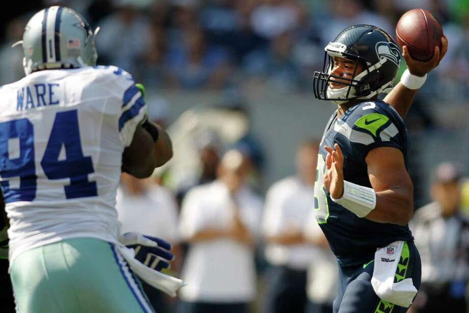 Seattle Seahawks quarterback Russell Wilson, right, throws under pressure from Dallas Cowboys' Demarcus Ware in the first half of an NFL football game, Sunday, Sept. 16, 2012, in Seattle. Photo: AP