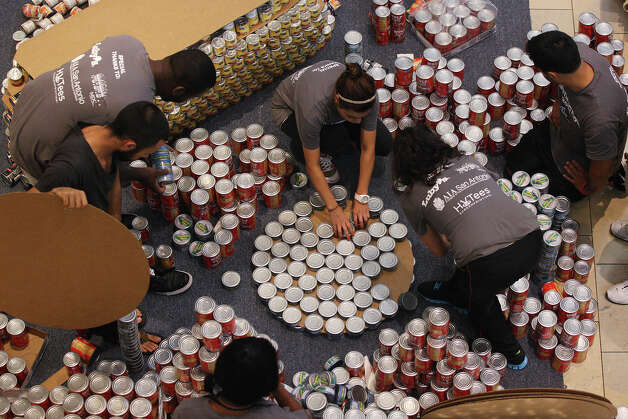 "Members of the San Antonio College American Institute of Architecture student chapter work on their entry at the 7th annual Canstruction at North Star Mall, Sunday, Sept. 16, 2012. Eleven teams of architects, engineers, general contractors and students used over 30,000 cans of food to create various designs. The students' entry was titlted, ""Big Red and Barbacoa taco."" Photo: Jerry Lara, San Antonio Express-News / © 2012 San Antonio Express-News"