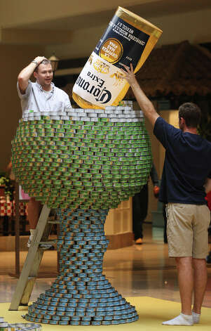 "Jeffery Watson, left, and Ryan Stewart work on the Alamo Architects and Turner Construction entry titled ""Can-o-rita,"" at the 7th annual Canstruction at North Star Mall, Sunday, Sept. 16, 2012. Eleven teams of architects, engineers, general contractors and students used over 30,000 cans of food to create various designs. Photo: Jerry Lara, San Antonio Express-News / © 2012 San Antonio Express-News"