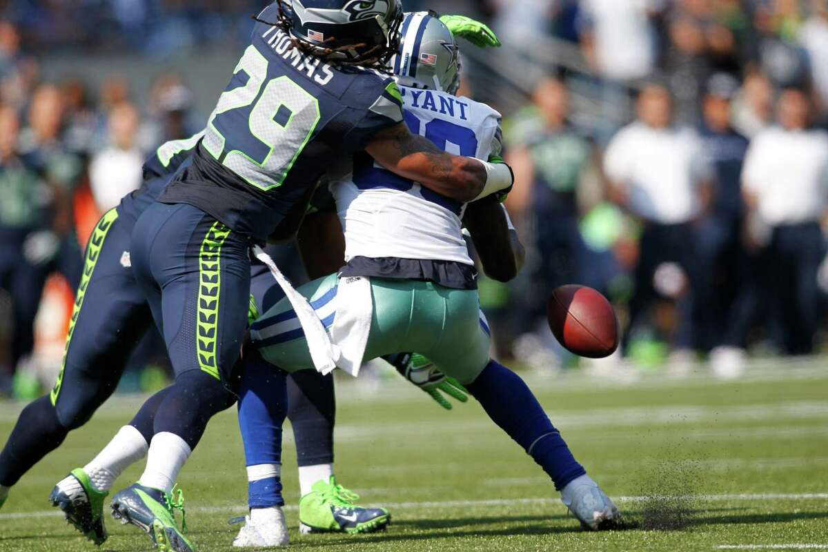 Receiver Dez Bryant drops a pass under pressure from Seattle defensive back and Texas-ex Earl Thomas in Sunday's loss.